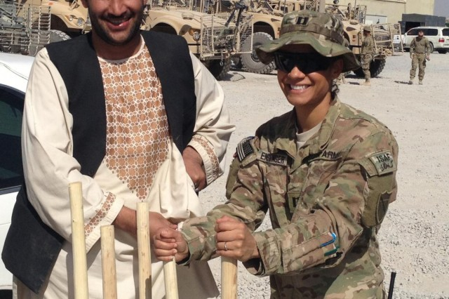 Capt. Varinka Barbini Ensminger receives materials from an Afghan contractor in October while deployed with the Kandahar Agri-business Development Team in Southern Afghanistan. The former National Guard Bureau women's marathon champion stayed busy in 2012, combining her military duties and her athletic training.