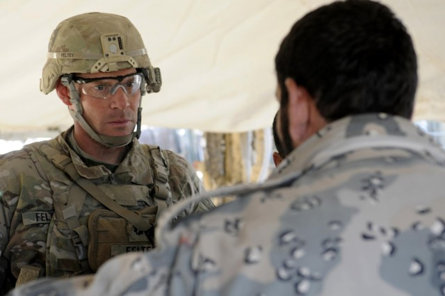 Lt. Col. Thomas Feltey, commander of 2nd Battalion, 23rd Infantry Regiment, speaks with Maj. Asmatullah Safi, an operations officer with the 3rd Zone Afghan Border Police, during Operation Southern Fist II, Afghanistan, Dec. 11. The purpose of the four-day operation was to neutralize enemy safe havens in Shorabak district, which is located in a remote area 55 miles south of Spin Boldak district near the Pakistan border.