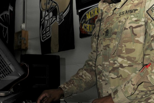 First Sgt. Tavares Garrett, first sergeant with 569th Engineer Company, plays music during the holiday celebration at the dining facility at Forward Operating Base Spin Boldak, Afghanistan, Dec. 23. The Morale, Welfare and Recreation team located at the base donated the prizes that were raffled out.