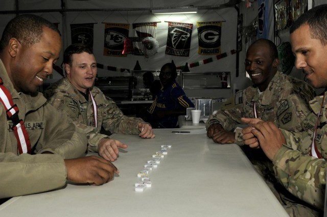 Soldiers with 569th Engineer Company enjoy a game of dominoes during the holiday celebration at the dining facility at Forward Operating Base Spin Boldak, Afghanistan, Dec. 23. The Morale, Welfare and Recreation team located at the base donated the prizes that were raffled out.