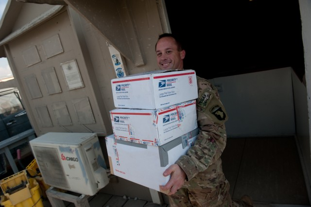 Sgt. Richard Candelario, B Company, 96th Aviation Support Battalion electronics technician carries packages out of the Task Force Destiny mailroom for delivery to Soldiers at Bagram Airfield, Afghanistan on Christmas Eve. (U.S. Army photo by Sgt. Duncan Brennan, 101st CAB public affairs)