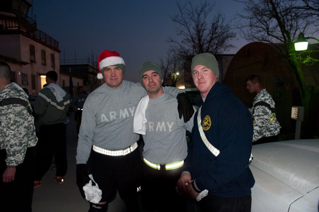 1st Sgt. Ronald Schlangen, first sergeant, Capt. Bimi Hoxha, commander, and Sgt. Bradley Rentz, repair and upkeep noncommissioned officer, Headquarters and Headquarters Company, 101st Combat Aviation Brigade take a moment to pose for a photo after running the 'Jingle Bell 5k' run at Bagram Airfield, Afghanistan Christmas morning. (U.S. Army photo by Sgt. Duncan Brennan, 101st CAB public affairs)