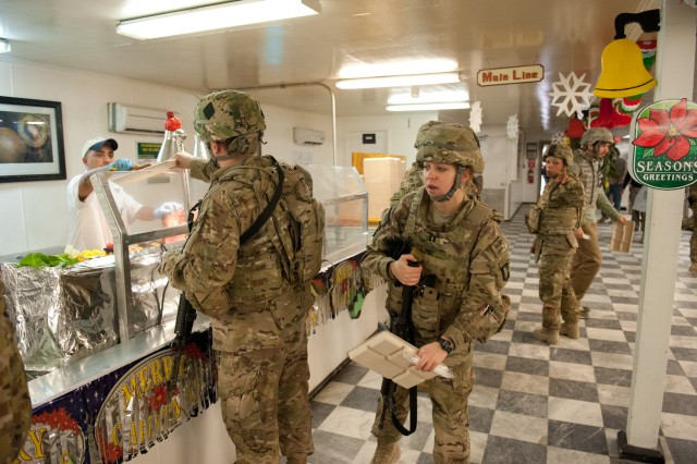 Capt. Patricia Lipke, Headquarters and Headquarters Company, 101st Combat Aviation Brigade air movement request officer-in-charge peers around a fellow Soldier to see what is being served during the holiday meal at the Kolle dining facility on Bagram Airfield, Afghanistan on Christmas day. (U.S. Army photo by Sgt. Duncan Brennan, 101st CAB public affairs)