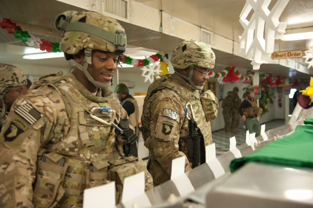 Sgt. Troy Cunningham, property book office noncommissioned-officer-in-charge, and Staff Sgt. Nelch Princivil, mobility noncommissioned-officer-in-charge with Headquarters and Headquarters Company, 101st Combat Aviation Brigade get served during the holiday meal at the Kolle dining facility on Bagram Airfield, Afghanistan on Christmas day. (U.S. Army photo by Sgt. Duncan Brennan, 101st CAB public affairs)