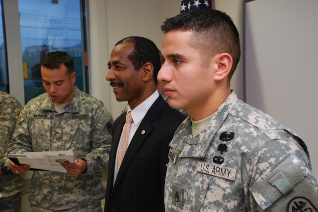 At right, Staff Sgt. Victor Miranda, Illesheim Health Clinic noncommissioned officer in charge, stands next to Director for Safety Mark G. Atkins, deputy assistant secretary of the Army, while Cpl. Marcus Murguia reads remarks for a certificate of appreciation.