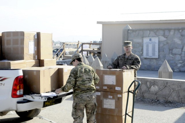 Spc. Rodney Wall and Sgt. Amanda Olmeda, 1st Brigade Combat Team, 101st Airborne Division (Air Assault), load 70-lb. boxes of holiday cheer onto a truck for transportation to the mail distribution facility of Forward Operating Base Fenty, Afghanistan.  The packages are destined for Soldiers in outlying locations across the Kunar and Nangarhar provinces of eastern Afghanistan.