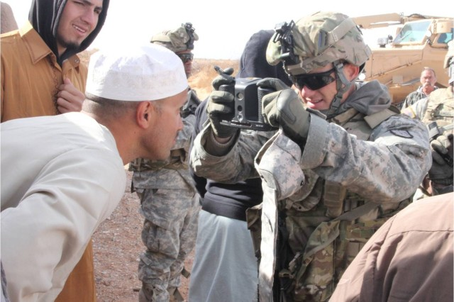 A Soldier in the 321st Engineer Company's Operations Intelligence Support Team collects biometrics of a role-played Afghan in Karmen'sha Village Dec. 15.