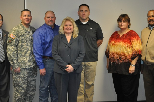 Debbie Wirt (fourth from left), a contract price/cost analyst and an LSS green belt at Iowa Army Ammunition Plant, led the transportation LSS project in an effort to earn an LSS black belt.  Robert Brewster, third from left, participated as a subject matter expert on the team to earn an LSS yellow belt. In addition to working on the project, both were required to complete additional training on LSS concepts.