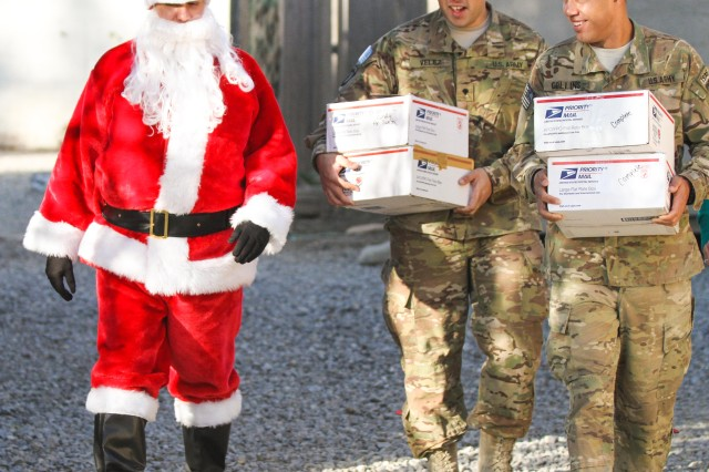 "Chief Warrant Officer 2 Brian Boase, an intelligence chief, Headquarters, Headquarters Company, 3rd Brigade Combat Team ""Rakkasans,"" 101st Airborne Division (Air Assault), walks alongside two Soldiers who are dressed as ""Santa's Helpers"" while they delivered care packages to the Soldiers and civilians of Forward Operating Base Salerno, in Khowst Province, Afghanistan, Dec. 25, 2012. Boase, along with his helpers, delivered more than 200 care packages to the Soldiers and civilians of FOB Salerno for Christmas."