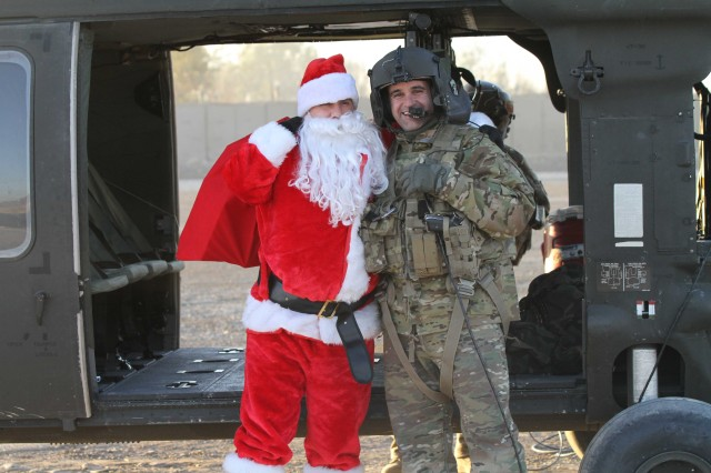 "KHOWST PROVINCE, Afghanistan - Chief Warrant Officer 2 Brian Boase, an intelligence chief, Headquarters, Headquarters Company, 3rd Brigade Combat Team ""Rakkasans,"" 101st Airborne Division (Air Assault), dresses as Santa Clause and poses with a UH-60 Blackhawk Helicopter crew chief after landing at Forward Operating Base Salerno, Afghanistan, Dec. 25, 2012. Boase, along with his helpers, delivered more than 200 care packages to the Soldiers and civilians of FOB Salerno for Christmas while dressed as Santa. (U.S. Army photo by Spc. Brian Smith-Dutton, Task Force 3/101 Public Affairs)"