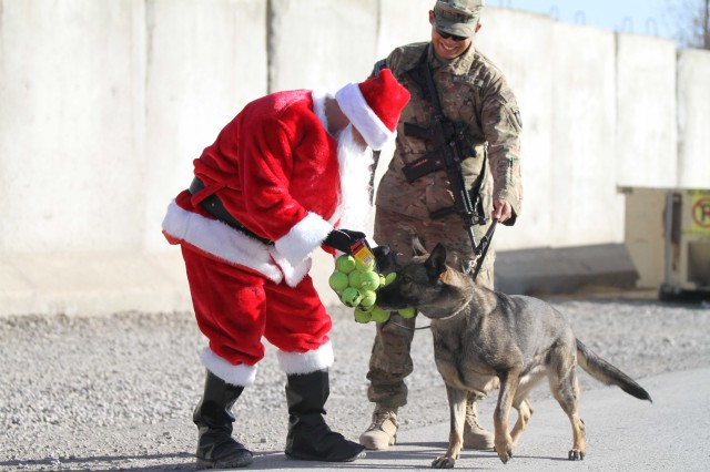 "KHOWST PROVINCE, Afghanistan - Chief Warrant Officer 2 Brian Boase, an intelligence chief, Headquarters, Headquarters Company, 3rd Brigade Combat Team ""Rakkasans,"" 101st Airborne Division (Air Assault), delivers tennis balls to a military working dog while dressed as Santa Clause at Forward Operating Base Salerno, Christmas day, Dec. 25, 2012. Boase dressed as Santa and delivered more than 200 care packages to the Soldiers and civilians of FOB Salerno for Christmas. (U.S. Army photo by Spc. Brian Smith-Dutton, Task Force 3/101 Public Affairs)"
