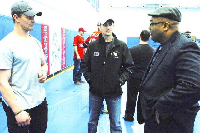 """Shane Hudella, center, founder of the nonprofit organization """"Defending the Blue Line,"""" which donates hockey equipment to military families, chats with Matt Hendricks, left, a National Hockey League player with the Washington Capitals, and a local hockey fan before a USO holiday tour show at Patch Barracks in Stuttgart, Germany, Dec. 17, 2012."""