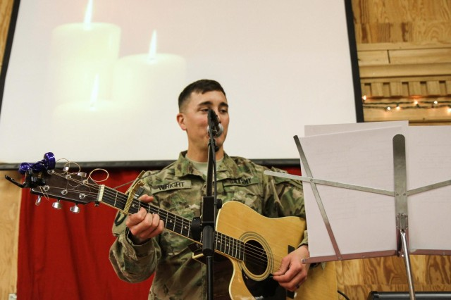"""First Lt. Michael Wright, an infantry officer assigned to 3rd Battalion, 187th Infantry Regiment, 3rd Brigade Combat Team """"Rakkasans,"""" 101st Airborne Division (Air Assault), plays a guitar during the candlelight service at Chapel Next on Forward Operating Base Salerno, Afghanistan, Dec. 24, 2012. Soldiers and civilians participated in the traditional Christmas service, celebrating the holiday season despite being deployed and away from their families."""