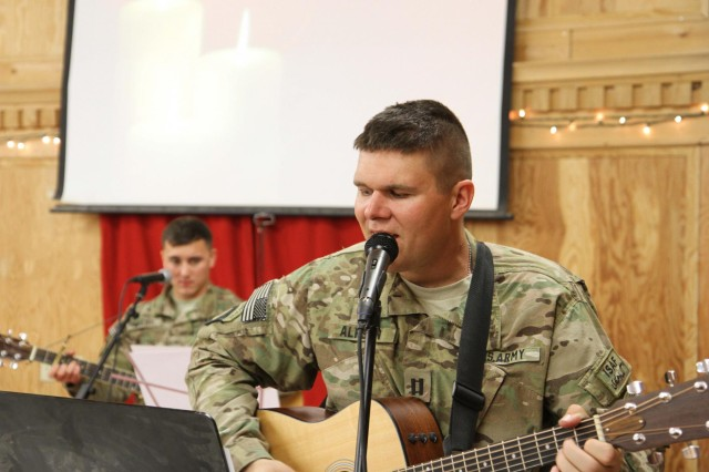 """Erik Alfsen, Battalion chaplain, 3rd Battalion, 187th Infantry Regiment, 3rd Brigade Combat Team """"Rakkasans,"""" 101st Airborne Division (Air Assault), plays a guitar during the candlelight service at Chapel Next on Forward Operating Base Salerno, Afghanistan, Dec. 24, 2012. Soldiers and civilians participated in the traditional Christmas service, celebrating the holiday season despite being deployed and away from their families."""