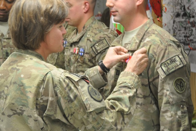 Brigadier General Kristin K. French, Joint Sustainment Command-Afghanistan commander, awards a Bronze Star Medal to Capt. William F. Fitzsimons, AFSBn-Kandahar redistribution and property assistance team, during an awards ceremony held Dec.22 at battalion headquarters. Fitzsimons is a member of the 4th Brigade Support Battalion, 27th Brigade Combat Team a New York Army National Guard unit who deployed from Apr. 15 to Dec. 30, 2012 to support the 401st AFSB retrograde missions.