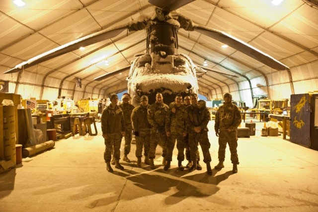 Crew chiefs on the night shift with 6th Battalion, 101st Combat Aviation Brigade, Task Force Shadow, pose with a CH-47 Chinook helicopter after pulling it into a hangar during a snowstorm at Bagram Air Field, Afghanistan, Dec. 27, 2012. (U.S. Army photo by Sgt. Duncan Brennan, 101st CAB public affairs)
