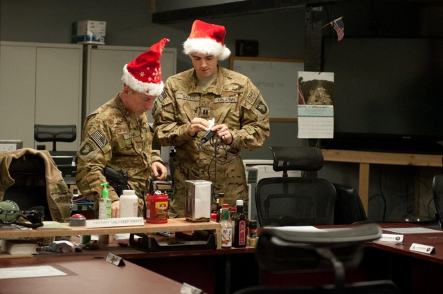 Capt. J.D. Sauer, commander, D Company, 6th Battalion, 101st Combat Aviation Brigade and Chief Warrant Officer 3 Tim Evans, production control officer, D, 6-101 mark equipment in the production control office near the helicopter flight line on Bagram Air Field, Afghanistan, on Christmas day. More senior members of the company took over day-to-day operations so that Soldiers had time to enjoy Christmas and spend time with their Families. (U.S. Army photo by Sgt. Duncan Brennan, 101st CAB public affairs)