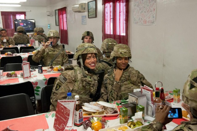 Spc. Dhayana Spinks, signal support systems specialist, and Pvt. 1st Class Boginskaya Battle, medical operations specialist, with Headquarters and Headquarters Company, 101st Combat Aviation Brigade pose for a picture after lunch at the Kolle dining facility on Bagram Air Field, Afghanistan Christmas day. (U.S. Army photo by Sgt. Duncan Brennan, 101st CAB public affairs)