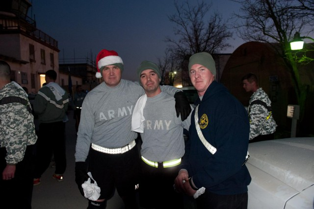 1st Sgt. Ronald Schlangen, first sergeant, Capt. Bimi Hoxha, commander, and Sgt. Bradley Rentz, repair and upkeep noncommissioned officer, Headquarters and Headquarters Company, 101st Combat Aviation Brigade take a moment to pose for a photo after running the 'Jingle Bell 5k' run at Bagram Air Field, Afghanistan Christmas morning. (U.S. Army photo by Sgt. Duncan Brennan, 101st CAB public affairs)