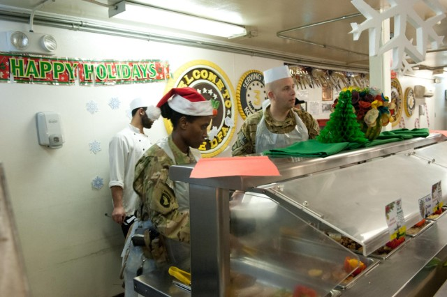 Sgt. Maj. Crystal Turner, operations sergeant major, and Lt. Col. Mark Weathers serve food at the Kolle dining facility's Christmas lunch at Bagram Air Field, Afghanistan on Christmas day. (U.S. Army photo by Sgt. Duncan Brennan, 101st CAB public affairs)