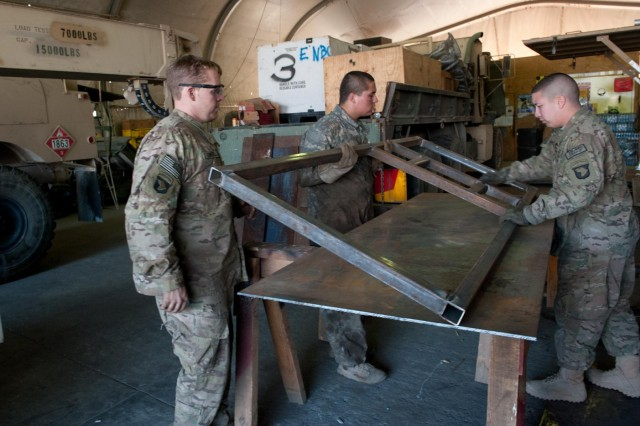 Soldiers from E Troop, 2nd Squadron, 17th Cavalry Regiment flip a steel frame into position onto a metal plate that will serve as a door in a gate on Forward Operating Base Fenty, Afghanistan, Dec. 11. (U.S. Army photo by Sgt. Duncan Brennan, 101st CAB public affairs)