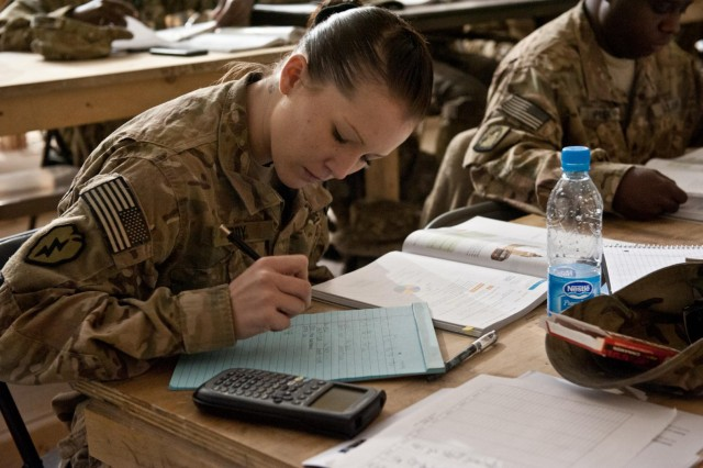 Spc. Amber Eddy, Headquarters and Headquarters company, 5th Battalion, 158th Aviation, aviation operations specialist, a native of Brigham City, Utah, takes notes and attempts to solve a problem posed to the the students during a class covering probability and statistics in a Task Force Ready classroom in Balkh province, Afghanistan, Nov. 14. (U.S. Army photo by Sgt. Duncan Brennan, 101st CAB public affairs)