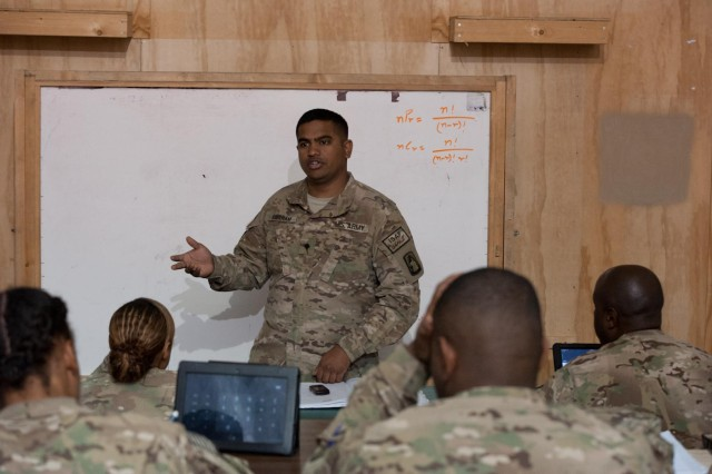 Spc. Vineeth Amaram, 12th Combat Aviation Brigade, Task Force Ready production control database administrator, a native of Hyderabad, India, teaches a math class encompassing probability and statistics in a classroom in the TF Ready footprint in Balkh province, Afghanistan on Nov. 14. (U.S. Army Photo by Sgt. Duncan Brennan, 101st CAB public affairs)