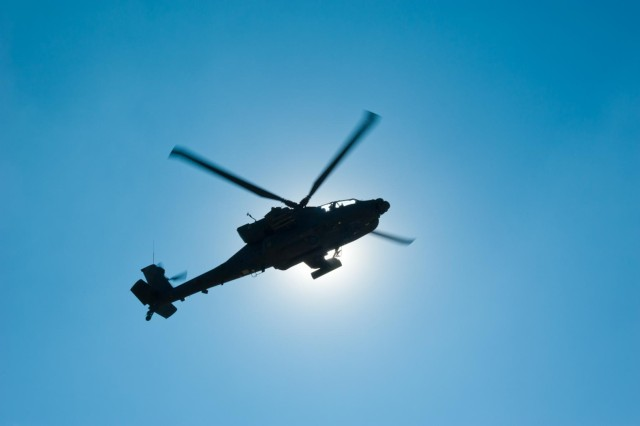 An AH-64 Apache helicopter hovers in front of the sun and conducts movement drills as part of a maintenance test flight in Kunduz province, Afghanistan, Nov. 19.