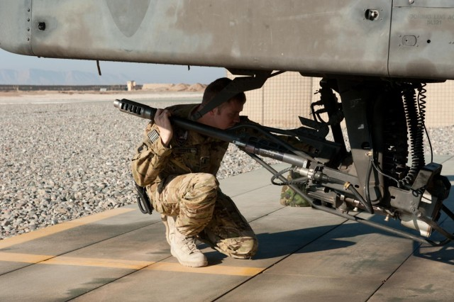 1st Lt. Austen Hoopes, C Company, 1st Battalion, 211th Aviation Regiment, Utah National Guard, inspects the 30 mm cannon on an Apache helicopter in Kunduz province, Afghanistan, Nov. 19.