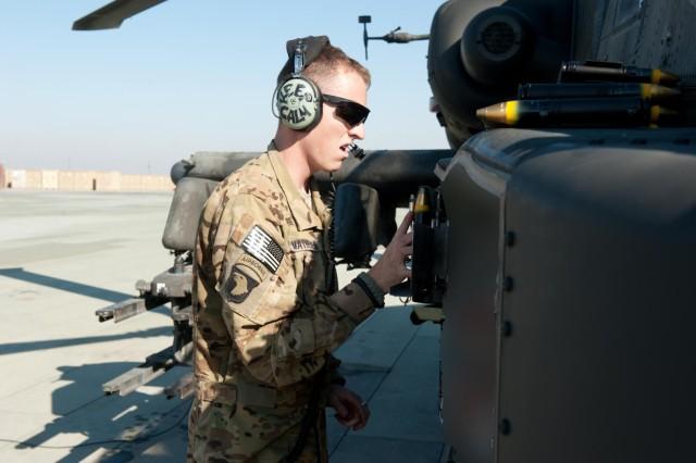 Spc. Casey Matheson, D Company, 1st Battalion, 211th Aviation Regiment, Utah National Guard, loads 30 mm ammunition into an AH-64 Apache helicopter before a maintenance test flight  in Kunduz province, Afghanistan, Nov. 19.