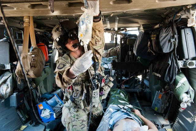 Spc. Thomas Appelhanz, C Company, 6th Battalion, 101st Combat Aviation Brigade flight medic, checks to ensure IV fluid is flowing properly to a wounded Afghan National Army soldier during a patient transfer mission at Kapisa province, Afghanistan, Nov. 5, 2012. (U.S. Army photo by Sgt. Duncan Brennan)