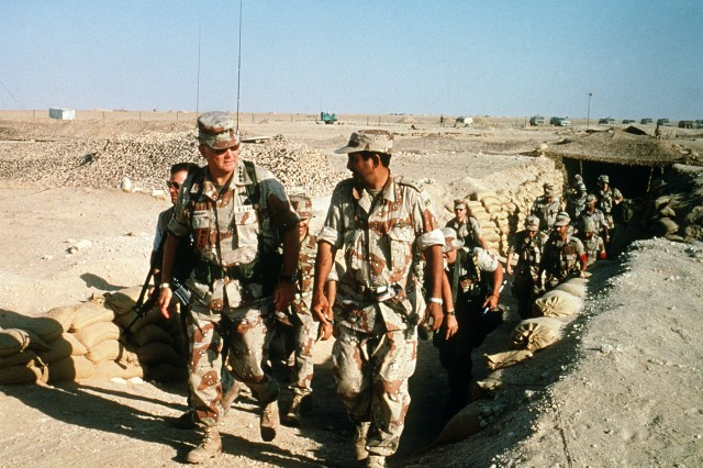 U.S. Army Gen. H. Norman Schwarzkopf, commander of U.S. Central Command, emerges from a camouflaged trench in the desert while visiting with troops from other countries during Operation Desert Shield, April 1, 1992.
