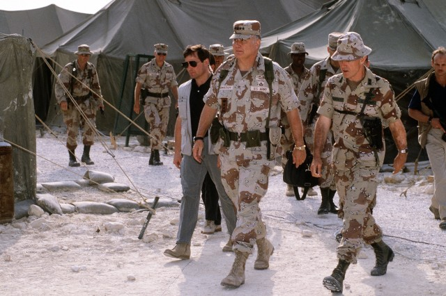 U.S. Army Gen. H. Norman Schwarzkopf, commander of U.S. Central Command, talks with U.S. Army Maj. Gen. Barry McCaffrey, commanding general, 24th Infantry Division (Mechanized), while at the tent city of the 18th Airborne Corps, Jan. 1, 1992. Schwarzkopf is visiting Allied units that took part in Operation Desert Storm.