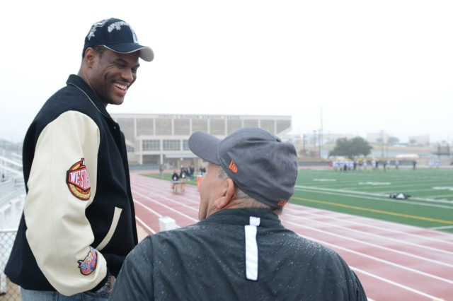 Former San Antonio Spurs center, David Robinson, speaks with another U.S. Army All-American West Team family member at the Blossom Athletic Center in San Antonio, Dec. 31, 2012. Robinson's son, Corey Robinson, number 88, earned his spot as wide-receiver for the West team while playing for San Antonio Christian School.
