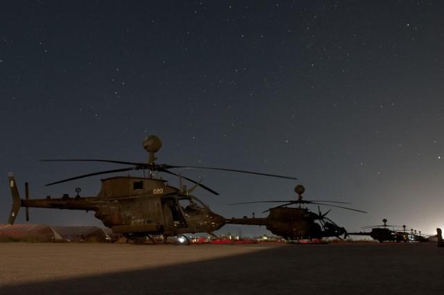 OH-58 Kiowa Warrior helicopters are kept mission ready as night falls on Forward Operating Base Fenty, Afghanistan, Dec. 19, 2012. (U.S. Army photo by Sgt. Duncan Brennan, 101st CAB public affairs)