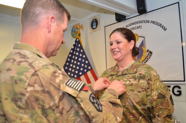 Lieutenant Colonel Teresa R. Bierd smiles as Col. Mark A. Paget, 401st Army Field Support Brigade commander, affixes the lieutenant colonel rank insignia to her uniform during her promotion ceremony held Dec. 26 at Logistics Civil Augmentation Program's Bagram headquarters. Bierd is newly arrived to her job as a LOGCAP support officer at Bagram Airfield.