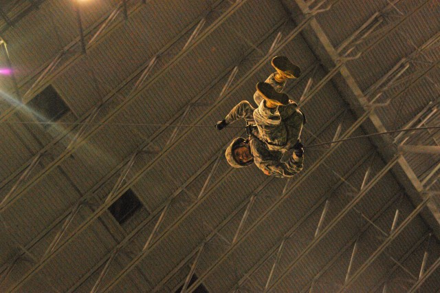 """Sgt. Michelle Sanchez makes her first rappel """"Hollywood style."""" She's the only female team member who came with the team to San Antonio. Nine rappelling instructors from the Air Assault School at Fort Campbell, Ky., practiced rappelling from the ceiling of San Antonio's Alamodome to the playing field, 180 feet below, Jan. 2, 2013. They were practicing for the U.S. Army All-American Bowl East-West game, which was played Jan. 5, 2013."""