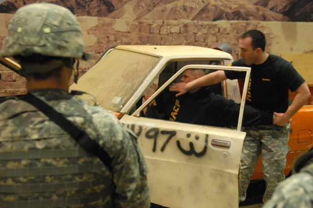 "Sgt. Miles Noonan (right), with the 174th Infantry Brigade, demonstrates how to properly extract a person from a vehicle during Modern Army Combatives training. Students formed teams and demonstrated the techniques that they learned in training to successfully clear buildings in a neighborhood and extract a ""high value target"" from a vehicle."