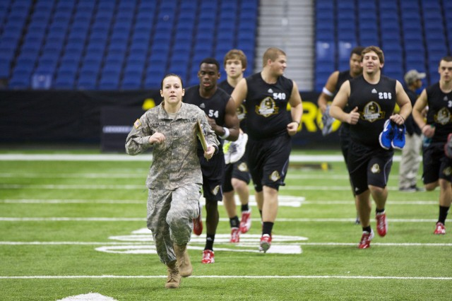Hillary Ashmead, a Cadet marshal from Boise State University, Idaho, leads participants in the National Combine, Jan. 4, 2013, to a station on the Alamodome field in San Antonio. She is one of 20 Army ROTC Cadets who served as marshals for the event.
