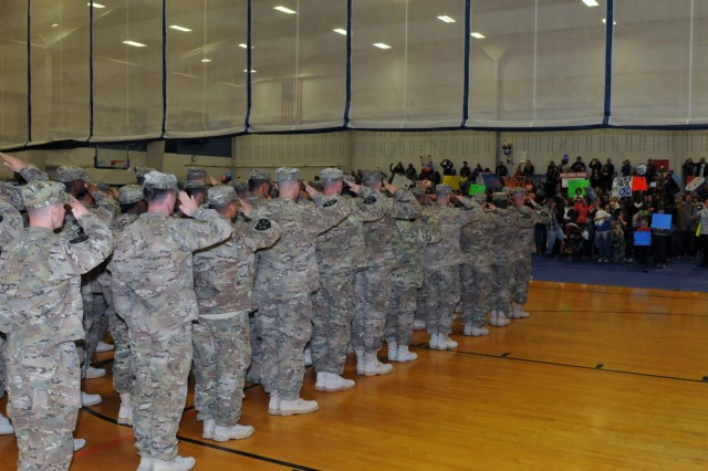Soldiers of the 2nd Infantry Brigade, 2nd Infantry Division, render a salute to their awaiting friends and family, members, as the curtain raises at JBLM's Wilson Fitness Center, Dec. 30, ending a nine-month combat deployment separation. Soldiers return from Afghanistan just in time for New Year's. (Photo by Sgt. Mark A. Cloutier)
