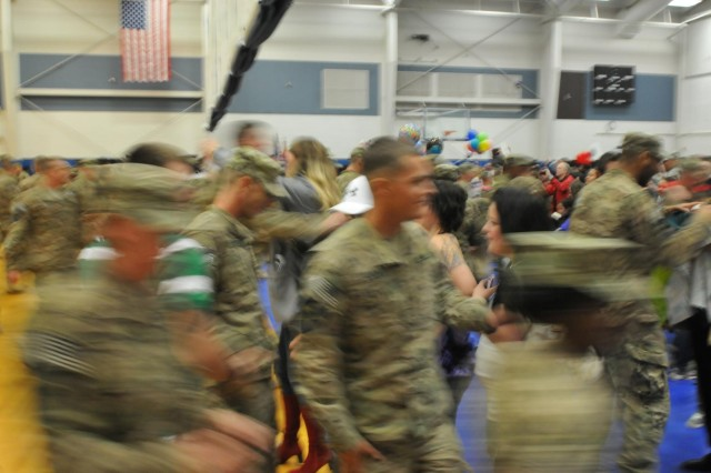 The currents of soldiers and family rush together, as the curtain in the gymnasium of JBLM's Wilson Fitness Center raises, closing the gap on a nine- month deployment separation. Soldiers of 2nd Infantry Brigade, 2nd Infantry Division, return home from Afghanistan, Dec. 30, just in time for the arrival of 2013.  (Photo by Sgt. Mark A. Cloutier)