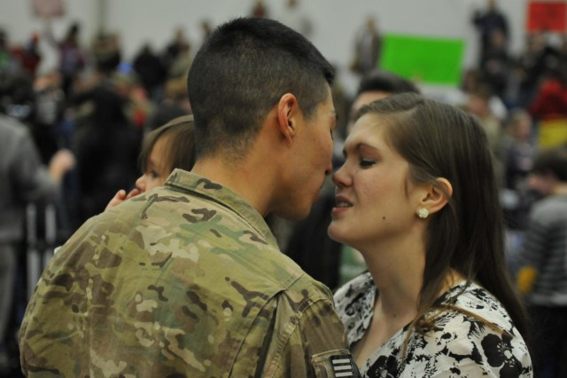 Soldier reunites with his wife and daughter at JBLM's Wilson Fitness Center, Dec. 30. Soldiers of 2nd Infantry Brigade, 2nd Infantry Division, return home from a nine-month deployment to Afghanistan, just in time for the arrival of 2013. (Photo by Sgt. Mark A. Cloutier)