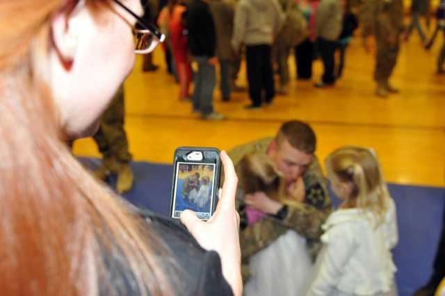 Chanel Sohl, wife of Capt. Jonathan Sohl, commander of B Company, snaps a keepsake photograph as her daughters reunite with their dad, at JBLM's Wilson Fitness Center, Dec. 30. Soldiers of 2nd Infantry Brigade, 2nd Infantry Division, return home from a nine-month deployment to Afghanistan, just in time for the arrival of 2013.  (Photo by Sgt. Mark A. Cloutier)