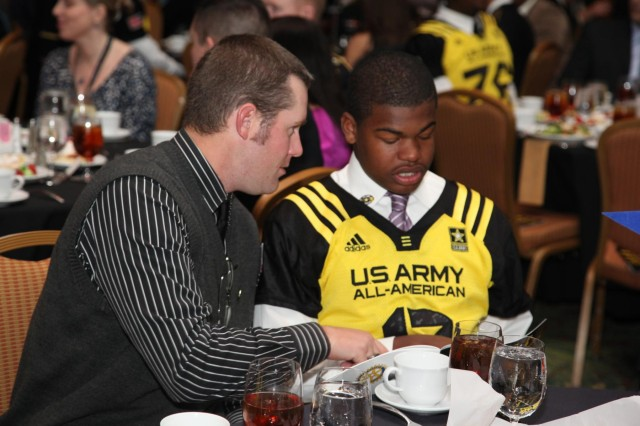 Assistant coach Nick Galbraith and defensive back Chris Hawkins from Rancho Cucamonga High School, Cucamonga, Calif., look through the awards program book at the 2013 U.S. Army All-American Bowl Awards Dinner at the Marriott Rivercenter Hotel in San Antonio, which celebrated the achievements of the All-American athletes, and honored Soldiers and their families, Jan. 4, 2013.