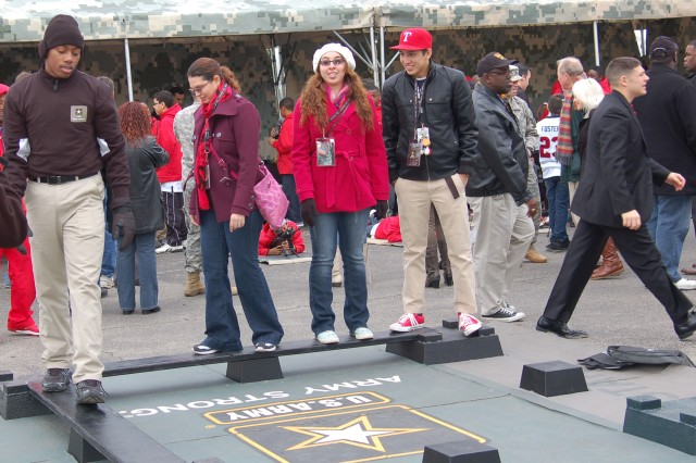 Visitors to the Army Strong Zone participate in a team building challenge. The Zone is a free, interactive area of dozens of exhibits that brings Army operations and programs to the American public.