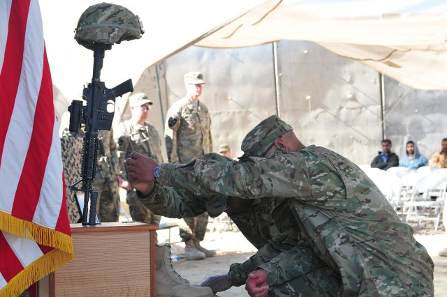 Capt. Jefferson Mason and 1st Sgt. Riley Seau, commander and first sergeant of 38th Engineer Company, Combined Task Force 4-2 (4th Stryker Brigade Combat Team, 2nd Infantry Division) touch the identification tags of Pfc. Markie Sims in remembrance during the memorial service for Sims Jan. 4, here. Sims, a combat engineer and Citra, Fla., native, died Dec. 29 during combat operations in the Panjwa'i district of Afghanistan. (U.S. Army photo by Sgt. Kimberly Hackbarth, 4th SBCT, 2nd Infantry Division Public Affairs Office)