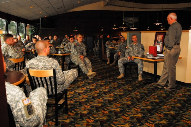 From right, Col. Michael J. Brokovich, retired, talks to Lt. Col. Charles H. Roede, commander for 1st Battalion, 377th Field Artillery Regiment, 17th Fires Brigade, and soldiers with the battalion after being inducted as the honorary commander of the 377th Field Artillery Regiment during an induction ceremony at the Cascade Community Club, Nov. 29. (U.S. Army photo by Spc. Nathan Goodall, 17th Fires Brigade Public Affairs)
