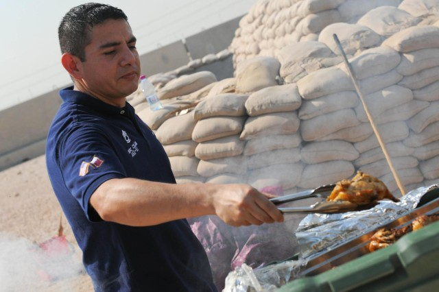 Sgt. 1st Class Cesar Ceja, the noncommissioned officer in charge of the personnel section for Area Support Group - Qatar, helps cook chicken during the Community Activity Center Christmas cookout, Dec. 9, 2012.