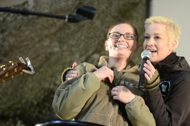 Country music singer Kellie Pickler invites Spc. Ashley S. Williams, an imagery analyst with Combined Joint Task Force-1, 1st Infantry Division, to sing with her for the troops as part of the USO Chairman of the Joint Chiefs of Staff Holiday Tour at Bagram Air Field, Afghanistan, Dec. 15, 2012. (U.S. Army photo by Staff Sgt. David J. Overson, 115th Mobile Public Affairs Detachment)