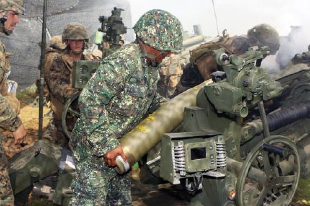 "Picatinny Arsenal munitions experts have developed a process to recycle a family of old artillery shells to create less expensive, more realistic and safer training rounds for Soldiers, giving new meaning to the slogan ""renew, reuse, recycle."" Pictured here, U.S. and Philippine Marines load M107 high explosive rounds into an M777A2 howitzer during an artillery shoot at Fort Magsaysay, Philippines, Oct. 25. The M1122 will replace the 155mm M804A1 Practice Projectile and M107 HE Projectile, which are more expensive, for training."